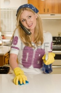 Blond caucasian woman wearing yellow cleaning gloves and bandana talking on the phone while using a spray cleaner and wiping the countertop in a kitchen Stock Photo - 3785626