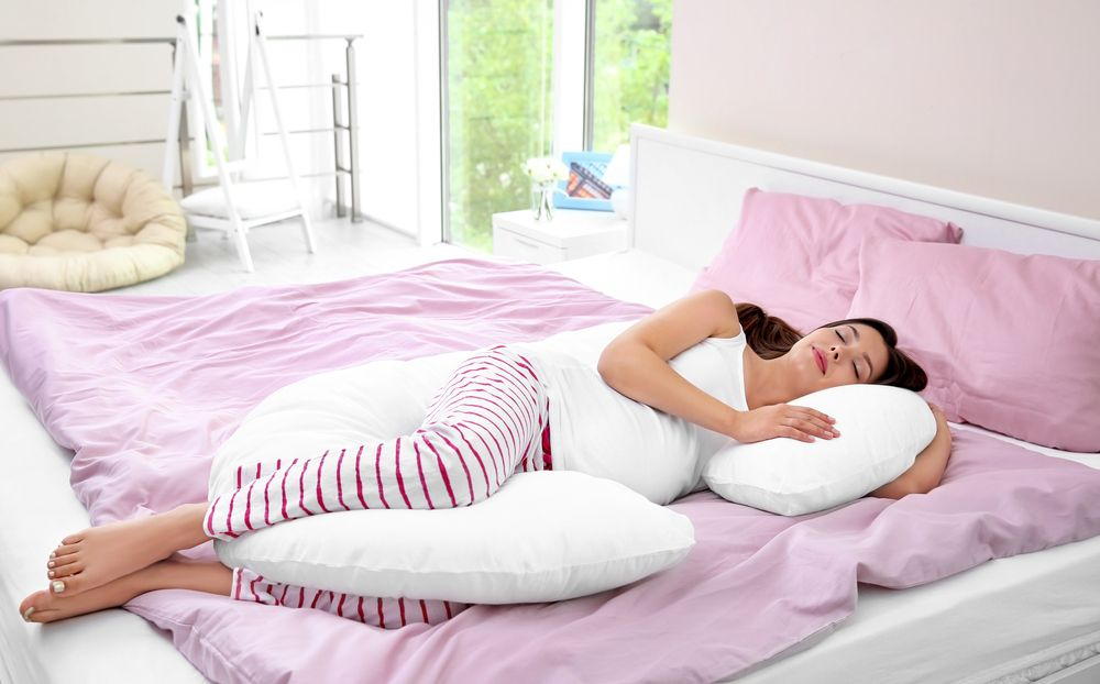 Pregnant woman with maternity pillow